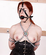 Redhead in leather corset - chained and gagged