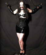 Black latex, corset, cuffs and bit-gag