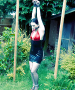 Latex brunette cuffed and chained outdoors