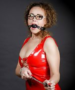 Latex cutie chains and gags herself